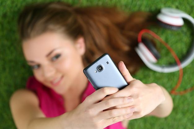 草の上に敷設する彼女のスマートフォンでセルフポートレートを取る若いきれいな女の子。電話に集中