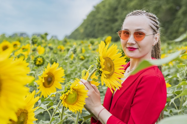 Young pretty girl walking on the sunflower field at sunset