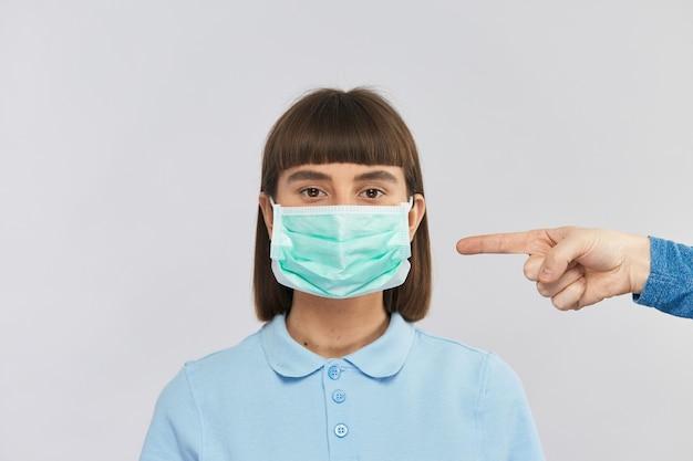 Молодая красивая девушка носит маску антивирусной защиты, а другой человек указывает на нее пальцем, вы должны защищать себя одноразовыми масками во время коронавируса, скопируйте пространство