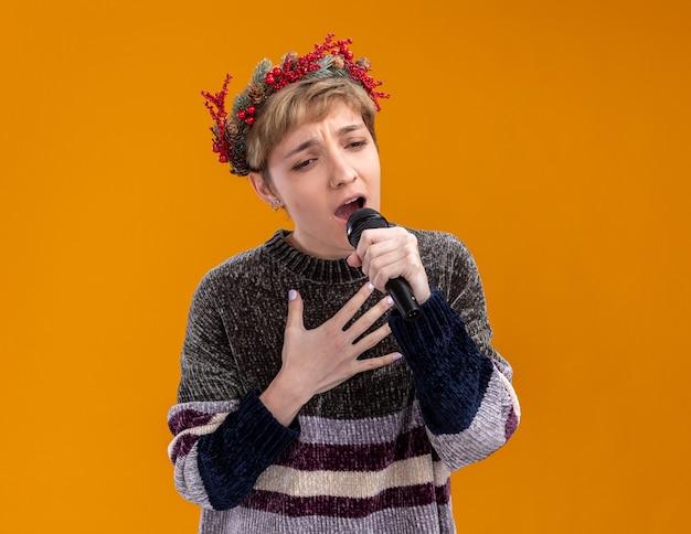 Молодая красивая девушка в рождественском венке с микрофоном, глядя вниз, держа руку на груди, поет на оранжевом фоне