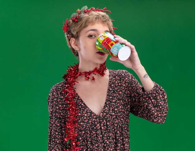 Young pretty girl wearing christmas head wreath and tinsel garland around neck drinking coffee from plastic christmas cup  isolated on green wall with copy space