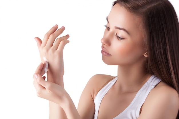 Молодая красивая девушка крем для рук на ее идеальных гладких руках. портрет лица включен