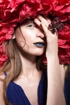 ハロウィーンパーティーのコスチュームで、変わった明るい服を着た若いかわいい女の子がメイクアップします。
