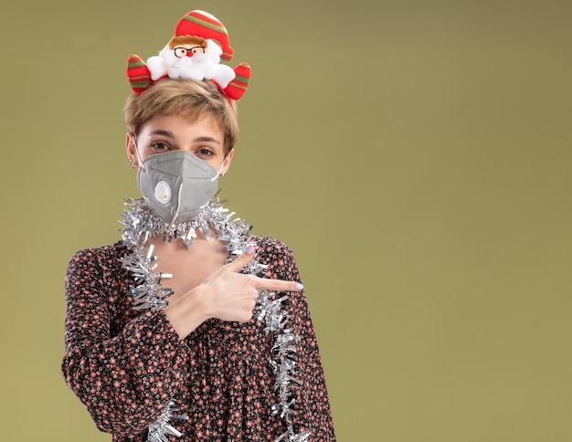 올리브 녹색 배경에 고립 된 측면에서 가리키는 카메라를보고 보호 마스크와 목 주위에 산타 클로스 머리띠와 반짝이 갈 랜드를 입고 젊은 예쁜 여자