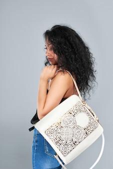 Молодая красивая девушка с черными вьющимися волосами в синих джинсах и черном мягком топе. она носит бело-коричневый рюкзак с интересным узором на плечах.