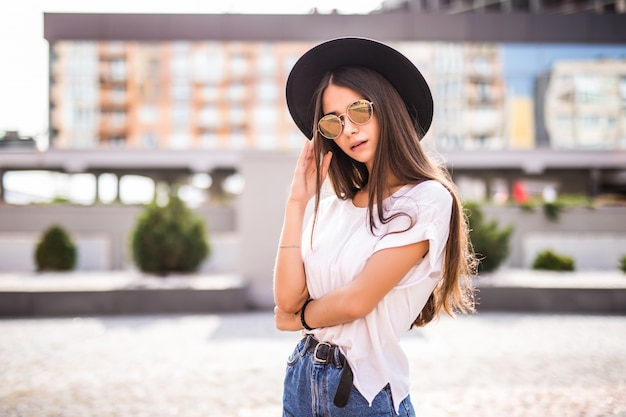 Young pretty girl with black hat and sunglasses outdoors on the sunny street