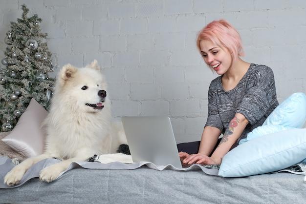 彼の大きな白い犬が付いているソファーの上のラップトップで働くブロンドの髪を持つ若いきれいな女の子。クリスマスツリーとうれしそうな表情。
