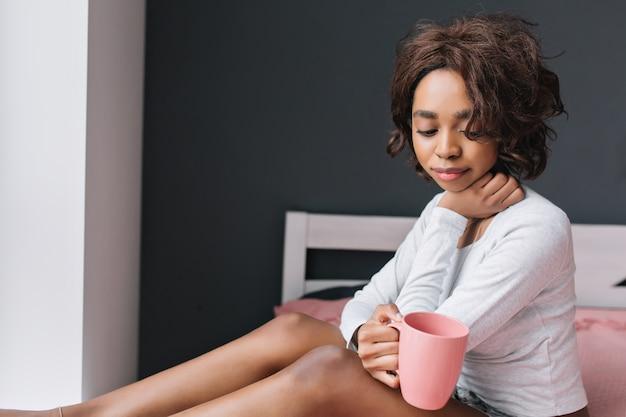 Молодая красивая девушка с чашкой кофе, чаем, наслаждаясь утром на кровати рядом с окном в комнате с серой стеной, розовым ковром на пространстве.