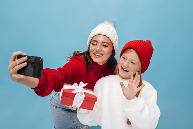 Young pretty girl with freckles in white shirt and red cap waving hand, hugging gift and takes selfie with her smiling sister