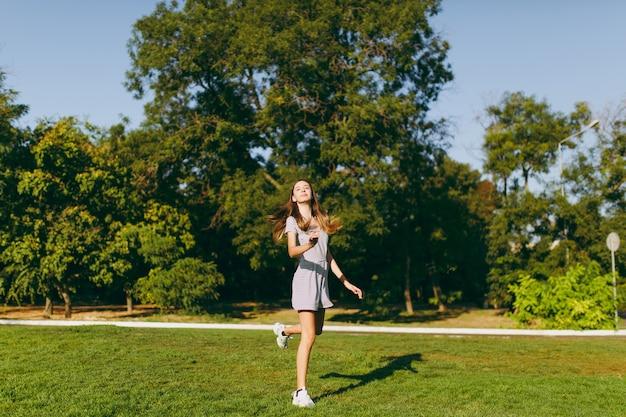 木の背景の公園の緑の芝生の草の上に滞在している明るい服に身を包んだ長い茶色の髪の若いかわいい女の子。夏の晴れた時間。