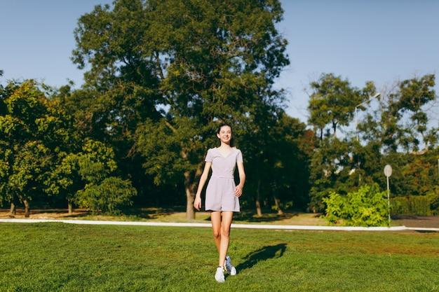 긴 갈색 머리를 가진 젊은 예쁜 소녀는 나무 배경에 있는 공원의 푸른 잔디 잔디에 머물고 있는 가벼운 옷을 입고 있습니다. 여름 화창한 시간입니다.
