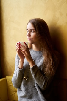Young pretty girl with long hair drinking coffee or tea  in the cafe.