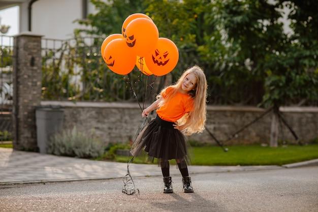 Молодая красивая девушка с длинными волосами в костюме, как маленькая ведьма, играющая и оборачивающаяся на улице с тыквенными воздушными шарами во время восхода солнца. концепция праздника.