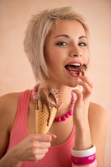 Young pretty girl with short blond hair eating melting chocolate ice cream in cone. 100% satisfaction