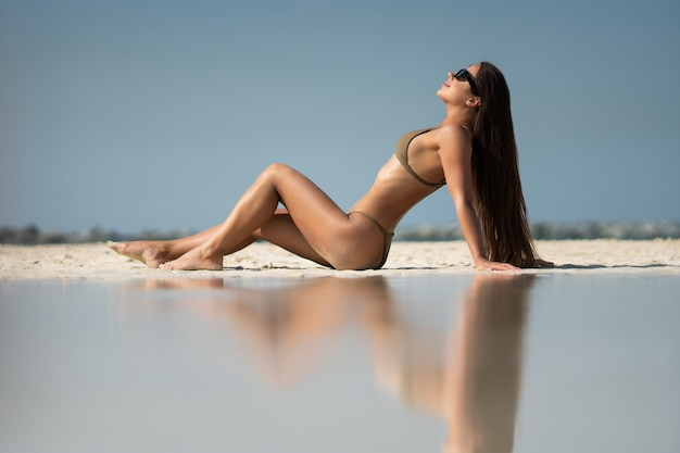 Young pretty girl with sunglasses lying on tropical beach