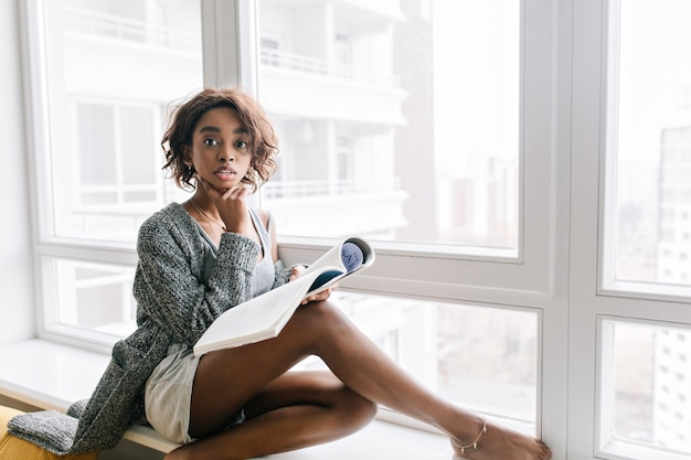 Young pretty girl with surprised look sitting on windowsill, big white window, reading magazine, book. wearing gray cardigan, singlet, shorts, gold bracelet on leg.