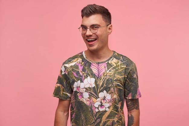 広い笑顔でカメラを見て、前向きで幸せで、花のtシャツとメガネを着て、ピンクの背景の上に立っている若いかわいい男