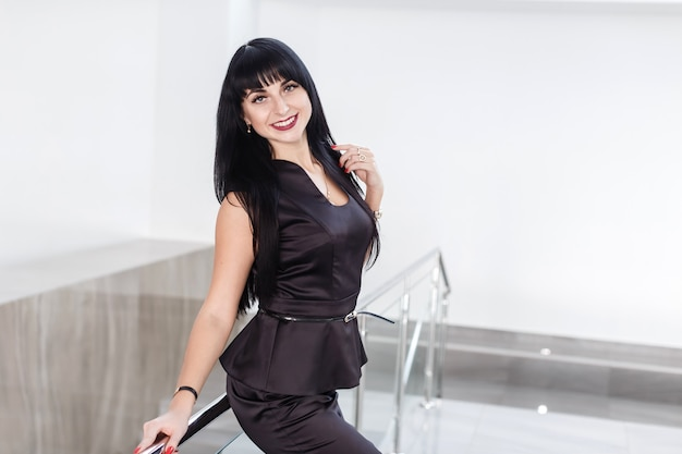 Young pretty happy brunette woman dressed in a black business suit with a short skirt is standing against the white wall in office leaning on railing, smiling, looking to camera.