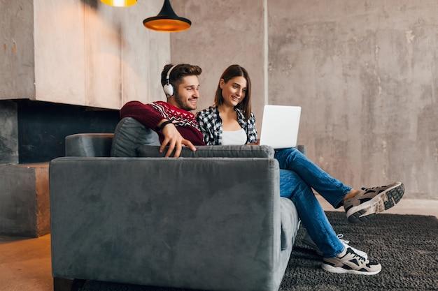 Молодой довольно счастливый улыбающийся мужчина и женщина, сидящие дома зимой, смотрящие в ноутбук, слушающие наушники, студенты, обучающиеся онлайн, пара вместе на досуге,