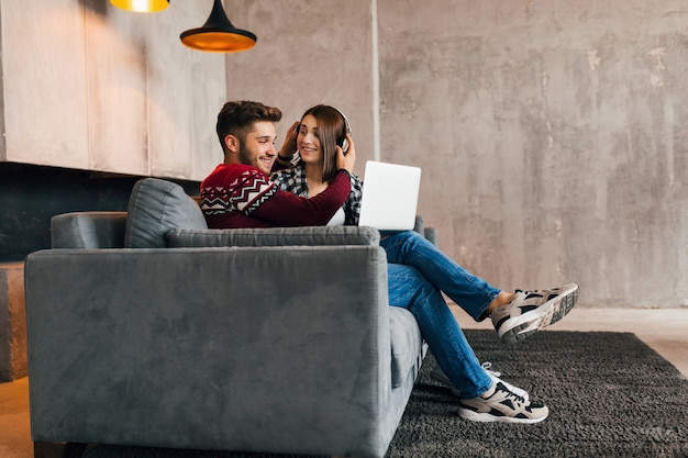 Young pretty happy smiling man and woman sitting at home in winter, looking in laptop, listening to headphones, students studying online, couple on leisure time together,