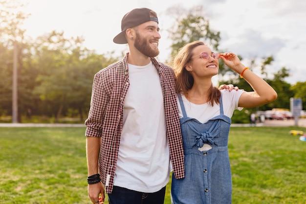 Coppia giovane piuttosto hipster che cammina nel parco, amici che si divertono insieme, romanticismo alla data, stile moda estiva, vestito colorato hipster, uomo e donna che sorridono abbracciando