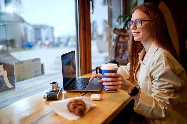 현대 노트북을 사용하여 카페에 앉아 빨간 머리를 가진 젊은 예쁜 힙스터 여성