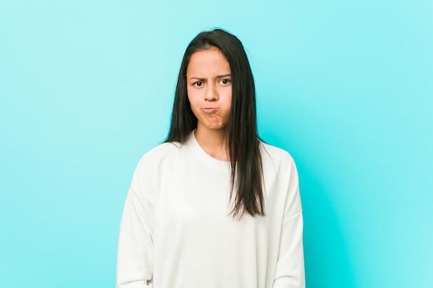 若いかなりヒスパニック系の女性は頬を吹く、疲れた表情をしています。表情のコンセプト。