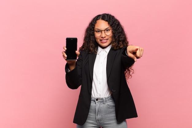 若いかなりヒスパニック系の女性のビジネスとスマートフォンの概念