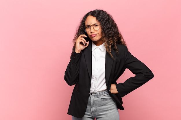 若いかなりヒスパニック系の女性、ビジネスとスマートフォンの概念