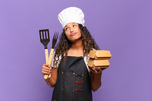 Young pretty hispanic woman confused expression barbecue chef concept