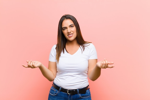 Young pretty hispanic woman feeling clueless and confused, not sure which choice or option to pick, wondering against pink wall