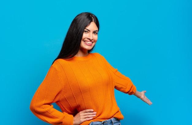 Молодая симпатичная латиноамериканка чувствует себя счастливой и веселой, улыбается и приветствует вас, приглашая вас дружелюбным жестом