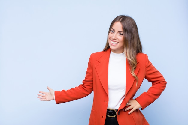 Young pretty hispanic woman feeling happy and cheerful, smiling and welcoming you, inviting you in with a friendly gesture against blue wall