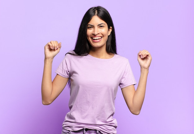 Молодая симпатичная латиноамериканка чувствует себя счастливой, позитивной и успешной, празднует победу, достижения или удачу