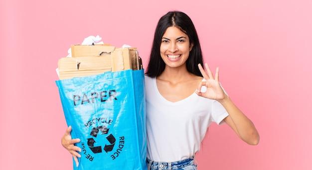 幸せを感じ、大丈夫なジェスチャーで承認を示し、リサイクルするために紙袋を持っている若いかなりヒスパニック系の女性
