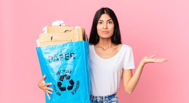 困惑し、混乱し、リサイクルするために紙袋を疑って保持していると感じている若いかなりヒスパニック系の女性