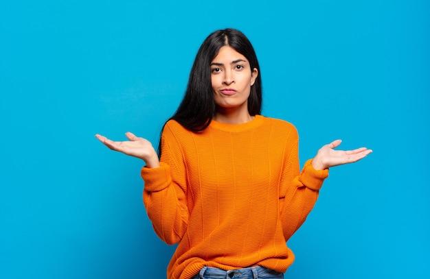Молодая симпатичная латиноамериканка чувствует себя озадаченной и сбитой с толку, сомневаясь, взвешивая или выбирая разные варианты со смешным выражением лица