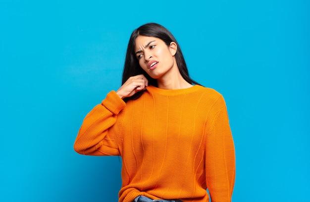 Молодая симпатичная латиноамериканка чувствует стресс, тревогу, усталость и разочарование, тянет за шею рубашки и выглядит разочарованной из-за проблемы