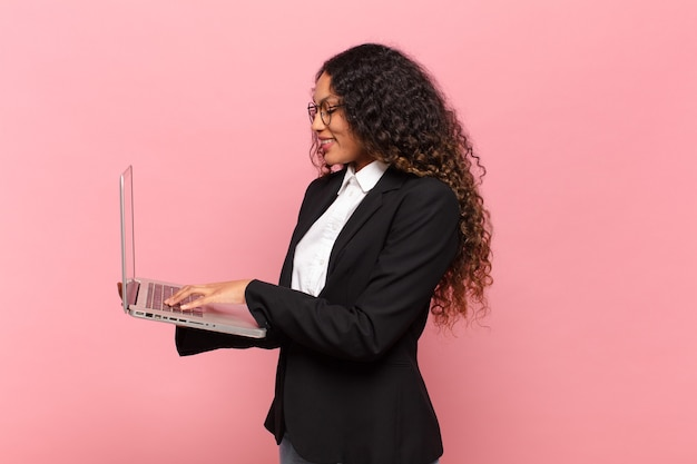 Young pretty hispanic woman. happy and surprised expression business and laptop cpncept