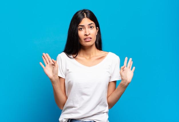 緊張し、心配し、心配そうに見える若いかなりヒスパニック系の女性は、私のせいではないと言ったり、私はそれをしなかった
