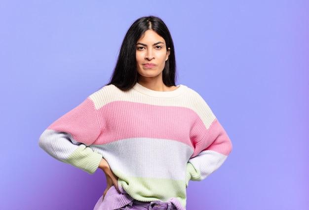 Молодая симпатичная латиноамериканка выглядит гордой, уверенной, крутой, дерзкой и высокомерной, улыбается и чувствует себя успешной