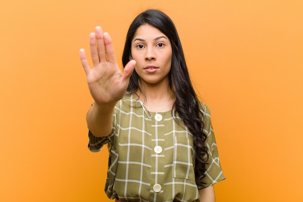 Young pretty hispanic woman looking serious, stern, displeased and angry showing open palm making stop gesture against brown wall