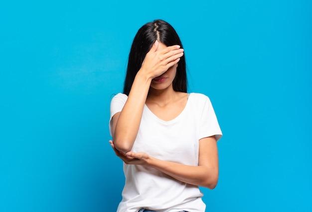 Молодая симпатичная латиноамериканская женщина выглядит напряженной, пристыженной или расстроенной, с головной болью, закрывая лицо рукой