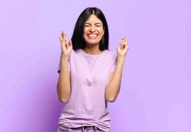 젊고 예쁜 히스패닉계 여성은 미소를 지으며 걱정스럽게 두 손가락을 교차시키며 걱정하고 행운을 빕니다.