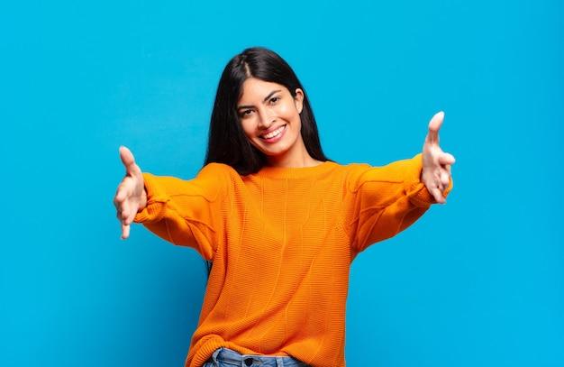 暖かく、フレンドリーで、愛情のこもった歓迎の抱擁を与え、幸せで愛らしい感じを元気に笑っている若いかなりヒスパニック系の女性