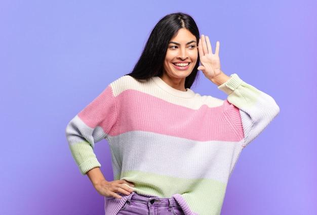 微笑んで、不思議なことに横を向いている若いかなりヒスパニック系の女性