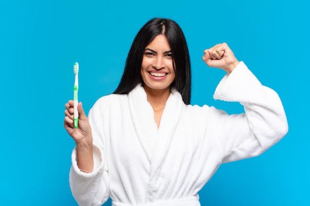 若いかなりヒスパニック系の女性。歯ブラシで