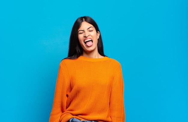 陽気な、のんきな、反抗的な態度、冗談を言ったり、舌を突き出したり、楽しんでいる若いかなりヒスパニック系の女性