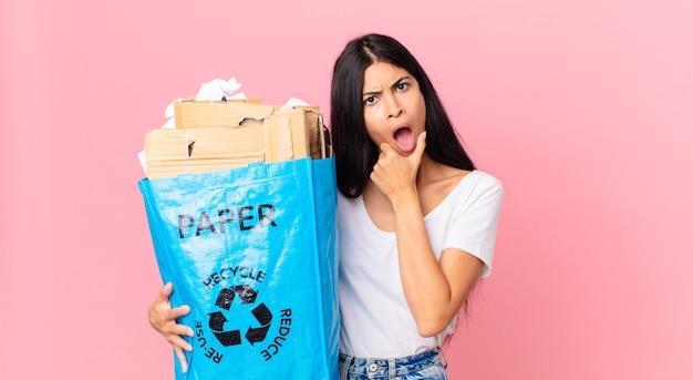 口と目を大きく開いて、あごに手を置き、リサイクルするために紙袋を持っている若いかなりヒスパニック系の女性