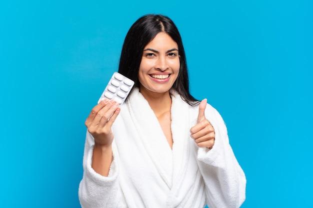 錠剤の錠剤を持つ若いかなりヒスパニック系の女性。病気の概念